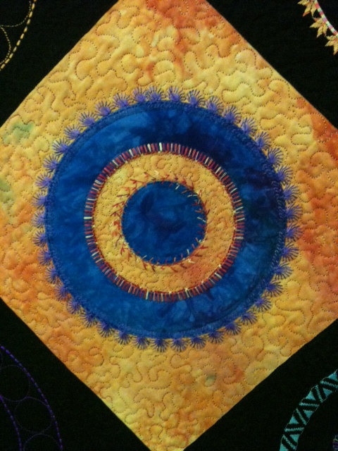PART OF ONE OF LIBBY LEHMAN'S PINATA QUILTS - DEC. STITCHING & APPLIQUE DONE WITH THE circular attachment.