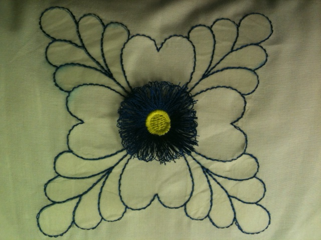 CLOSE UP OF THE QUILINT DESIGN EMBROIDERED IN THE HOOP WITH CUTE FRINGE FLOWER ADDED TO THE CENTER